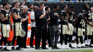 The New Orleans Saints stand during the National Anthem before their game against the Carolina Panthers