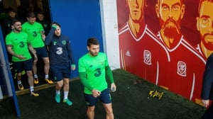 Wes Hoolahan walks by the murals of Wales stars at the Cardiff City Stadium