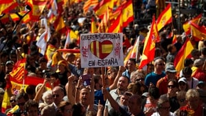 A man holds a card that says 'We want Catalonia in Spain'