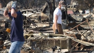 Ben Pederson (R) looks for salvageable items in the remains of his family's home was destroyed by wildfire in Santa Rosa