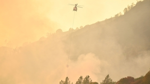 A helicopter attempts to extinguish flames in Calistoga by dropping water