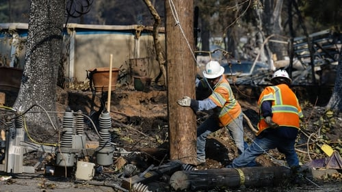 Workers repair power lines following the damage caused by the fire in Santa Rosa, California