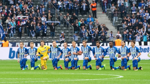 Players from Hertha Berlin take a knee before a Bundesliga game.