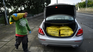 A man at Dublin Bay loads the boot of a car with sandbags to protect homes