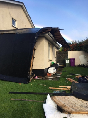 Debris scattered around a garden  in Ballinteer, Dublin after a roof is ripped off a house