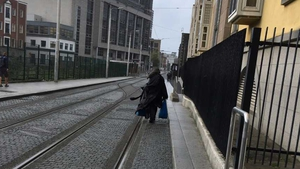 A homeless man who sleeps rough in Dublin walking along the Luas line near the Four Courts
