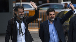 Jordi Sanchez and Jordi Cuixart wave to supporters as they arrive at the court in Madrid