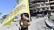 A Syrian Democratic Forces commander waves her group's flag in Al-Naim square in Raqqa