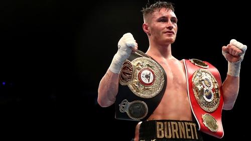 Ryan Burnett celebrates with his IBF and WBA belts