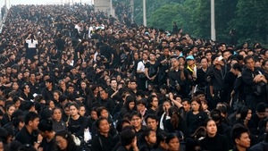 Thousands of people queue on a bridge to attend the funeral of the late Thai King Bhumibol Adulyadej