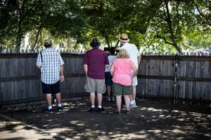 Tourists visit the grassy knoll in Dealey Plaza, which is often cited as a location for an additional shooter