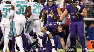 Baltimore Ravens quarterback Joe Flacco (5) is helped up by Matt Skura (68) after taking a hard hit and leaving the game against the Miami Dolphins