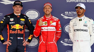 Sebastian Vettel, flanked by Max Verstappen (L) and Lewis Hamilton (R), celebrates his pole