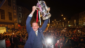 Achille Campion lifts the FAI Cup trophy in front of the waiting Cork City fans