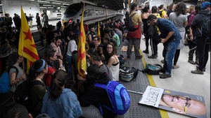 Protesters hold a picture of deposed Catalan regional government's foreign relations chief Raul Romeva reading 'Freedom' as they block train tracks at the Sants Station in Barcelona