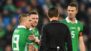 Northern Ireland players surround the referee after a penalty is awarded.