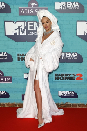 Looks like Rita Ora in a hurry to get to the red carpet. She wore a white bathrobe with a towel around her head and some outstanding jewellery.