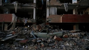 A flattened vehicle underneath building rubble is seen following the earthquake