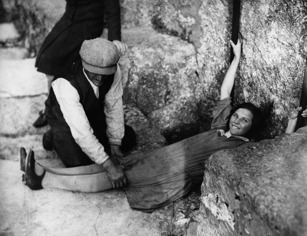 1930 A girl lies flat on the ground, in order to kiss the Blarney Stone in Blarney Castle, Cork city