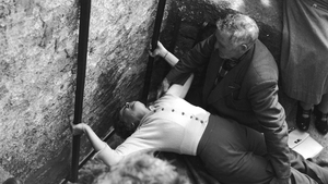 1950: With the help of the curator of the stone, a woman bends to kiss the Blarney Stone at Blarney Castle in County Cork.