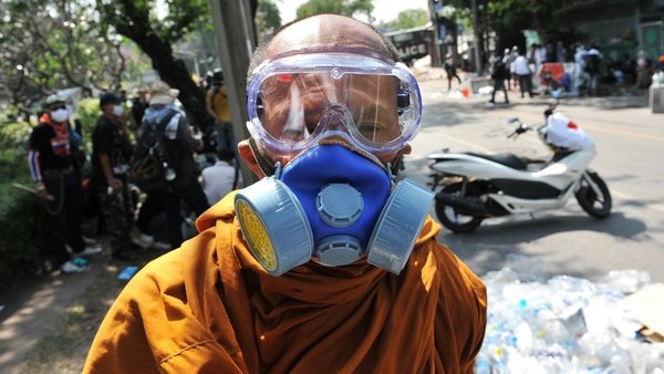 A Buddhist monk wearing a gas mask during protests in Bangkok in December 2013. Photo: Rufus Cox/Getty Images
