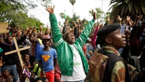 People react to a military helicopter overhead as they make their way towards Robert Mugabe's residence