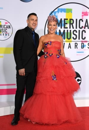 Carey Hart and Pink were all smiles on the red carpet. Carey wore a black suit with blue tie while Pink wore a Monique Lhuillier gown.