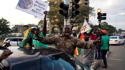 People celebrate in Harare after Robert Mugabe announced his resignation as Zimbabwe's President