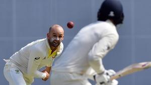 Australia's Nathan Lyon (L) bowls to England's batsman James Vince (R)