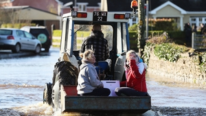 A tractor helps women through the floods in Mountmellick, Co Laois