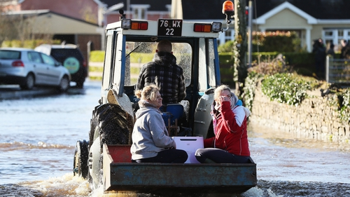 A tractor helps women through the recent floods in Mountmellick, Co Laois