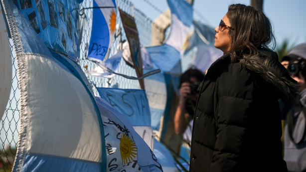 A woman looks at messages for the safe return of the missing crew