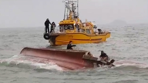Rescuers conduct a search operation for missing people following the collision