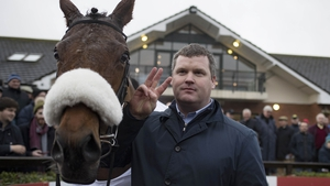 Trainer Gordon Elliott poses with Death Duty to celebrate winning the three Grade One races on the card