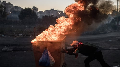 A burning dumpster is pushed down a street to make a barricade during clashes near an Israeli checkpoint in Ramallah, West Bank