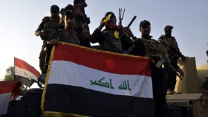 Iraqi soldiers display a flag in central Mosul
