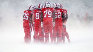 The Buffalo Bills offense huddles together in freezing conditions