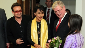 Aung San Suu Kyi and Bono meet Eamon Gilmore as she is presented with flowers upon her arrival at Dublin Airport in 2012