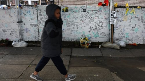 A young boy walks past tributes to Grenfell Tower residents in west London