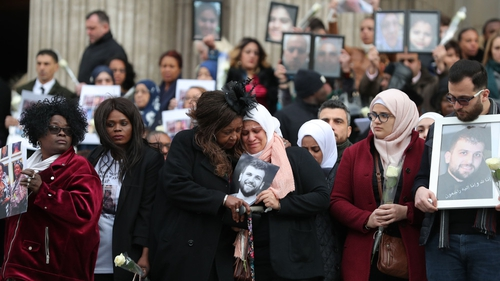 Photos of those who died are held by relatives