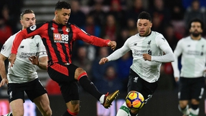 Joshua King (C) holds off Liverpool's Jordan Henderson (L) and Alex Oxlade-Chamberlain
