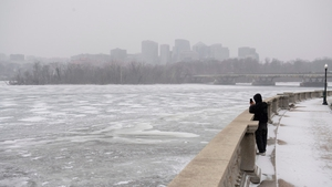 A man photographs the frozen Potomac River during a snow storm in Washington, DC