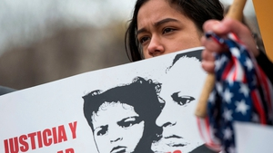 A young girl looks on during a protest near the White House over plans to end TPS for Salvadorans