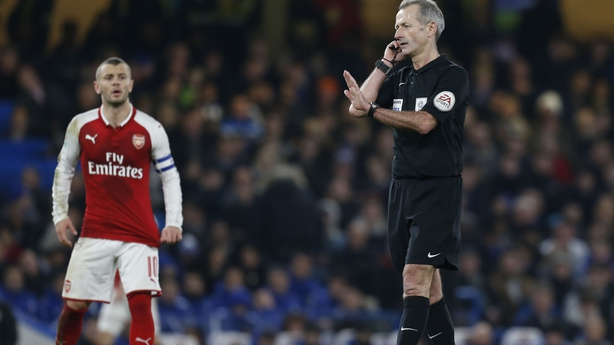 Martin Atkinson stops play to consult with the Video Assistant Referee during the English League Cup semi-final first leg