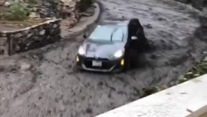 The car had its lights and wipers on as it was pushed through the street