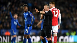 Referee Jon Moss in communication with the video assistant referee in the Leicester-Fleetwood clash