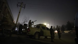 Afghan security officials take up positions near the scene of attack in Kabul