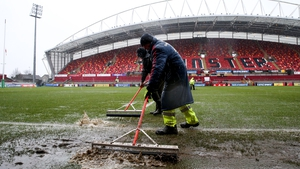 Ground staff remove excess water from the pitch at Thomond Park