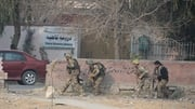 Afghan army soldiers take positions near the building
