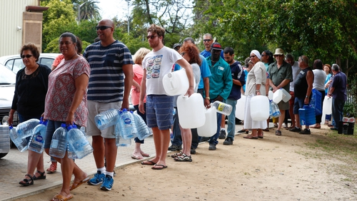 Residents queue for water at a mountain spring collection point